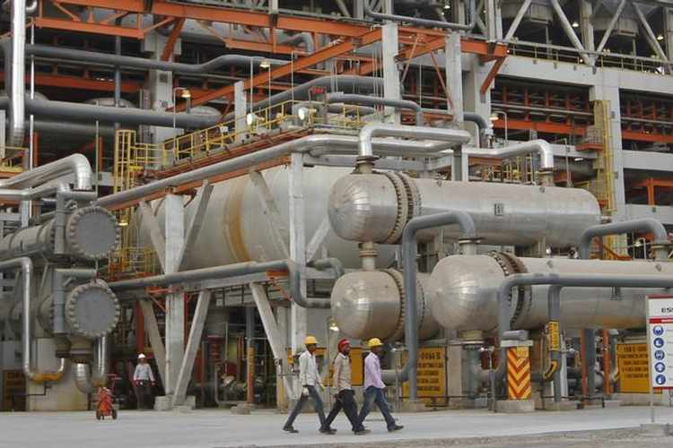 Workers walk inside the complex of the Vadinar refinery operated by Essar Oil Ltd. in Gujarat